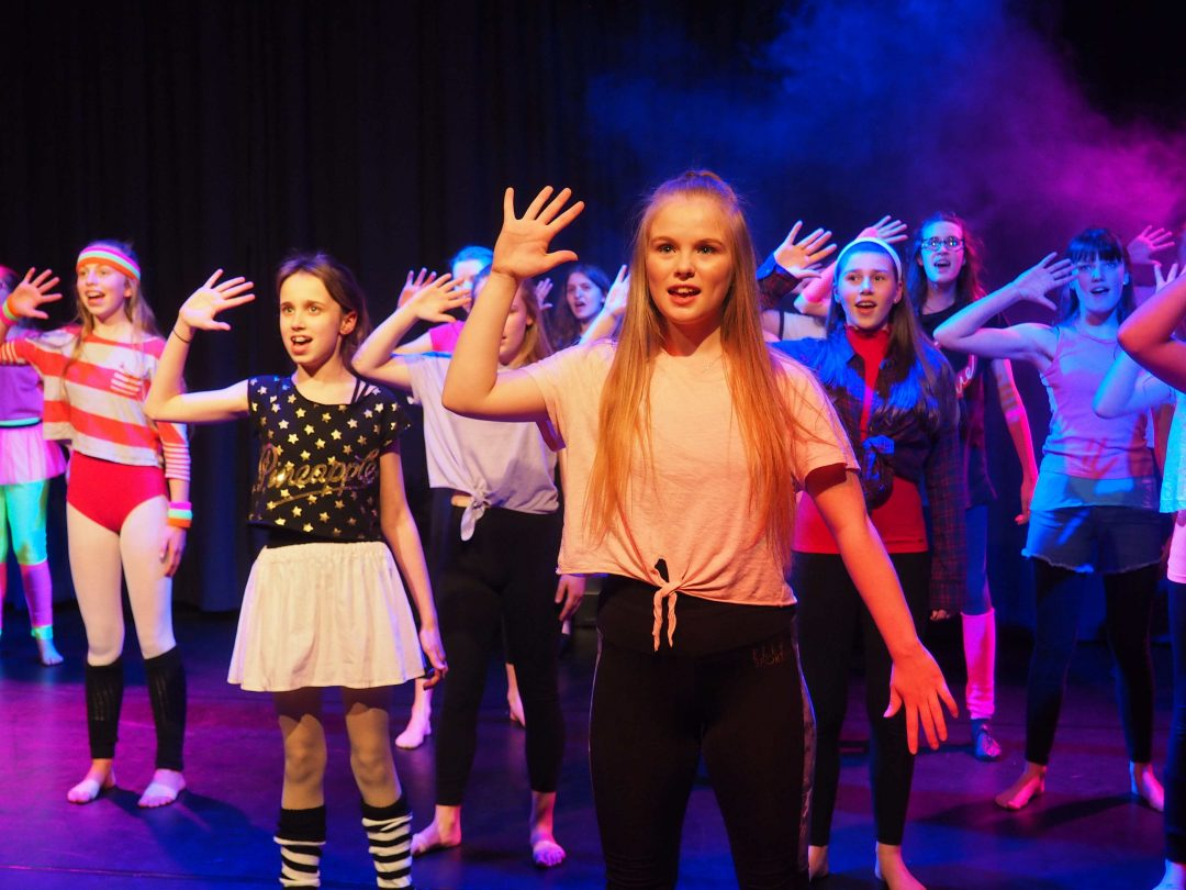 Musical Theatre group singing and dancing to Fame